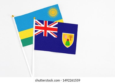 Turks And Caicos Islands and Rwanda stick flags on white background. High quality fabric, miniature national flag. Peaceful global concept.White floor for copy space.