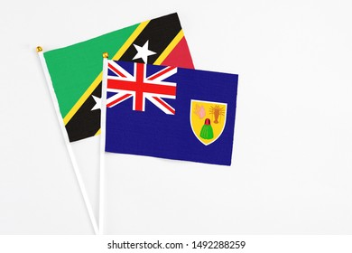 Turks And Caicos Islands and Saint Kitts And Nevis stick flags on white background. High quality fabric, miniature national flag. Peaceful global concept.White floor for copy space.
