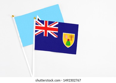 Turks And Caicos Islands and Saint Lucia stick flags on white background. High quality fabric, miniature national flag. Peaceful global concept.White floor for copy space.