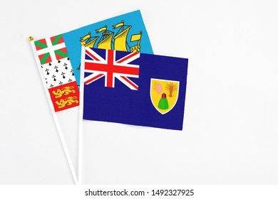 Turks And Caicos Islands and Saint Pierre And Miquelon stick flags on white background. High quality fabric, miniature national flag. Peaceful global concept.White floor for copy space.