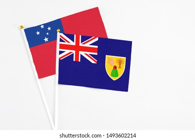 Turks And Caicos Islands and Samoa stick flags on white background. High quality fabric, miniature national flag. Peaceful global concept.White floor for copy space.