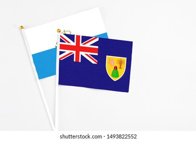 Turks And Caicos Islands and San Marino stick flags on white background. High quality fabric, miniature national flag. Peaceful global concept.White floor for copy space.