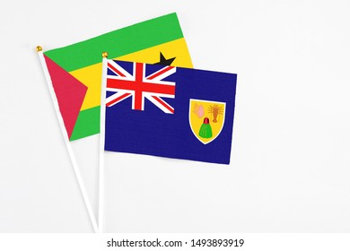 Turks And Caicos Islands and Sao Tome And Principe stick flags on white background. High quality fabric, miniature national flag. Peaceful global concept.White floor for copy space.