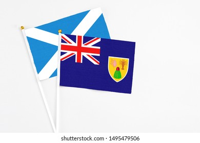 Turks And Caicos Islands and Scotland stick flags on white background. High quality fabric, miniature national flag. Peaceful global concept.White floor for copy space.