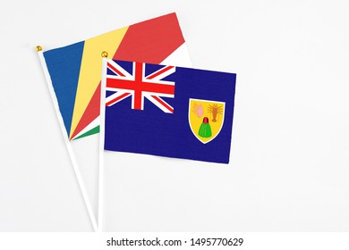 Turks And Caicos Islands and Seychelles stick flags on white background. High quality fabric, miniature national flag. Peaceful global concept.White floor for copy space.v