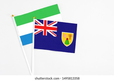 Turks And Caicos Islands and Sierra Leone stick flags on white background. High quality fabric, miniature national flag. Peaceful global concept.White floor for copy space.