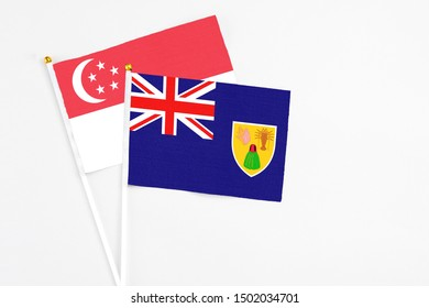 Turks And Caicos Islands and Singapore stick flags on white background. High quality fabric, miniature national flag. Peaceful global concept.White floor for copy space.