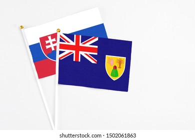 Turks And Caicos Islands and Slovakia stick flags on white background. High quality fabric, miniature national flag. Peaceful global concept.White floor for copy space.