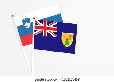 Turks And Caicos Islands and Slovenia stick flags on white background. High quality fabric, miniature national flag. Peaceful global concept.White floor for copy space.