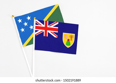 Turks And Caicos Islands and Solomon Islands stick flags on white background. High quality fabric, miniature national flag. Peaceful global concept.White floor for copy space.