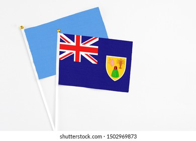 Turks And Caicos Islands and Somalia stick flags on white background. High quality fabric, miniature national flag. Peaceful global concept.White floor for copy space.