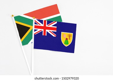 Turks And Caicos Islands and South Africa stick flags on white background. High quality fabric, miniature national flag. Peaceful global concept.White floor for copy space.