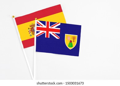 Turks And Caicos Islands and Spain stick flags on white background. High quality fabric, miniature national flag. Peaceful global concept.White floor for copy space.