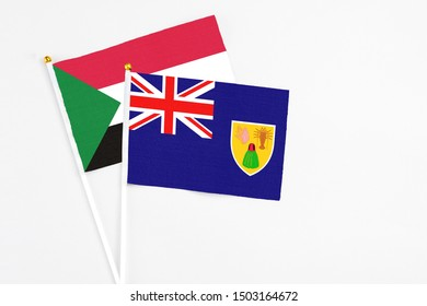 Turks And Caicos Islands and Sudan stick flags on white background. High quality fabric, miniature national flag. Peaceful global concept.White floor for copy space.