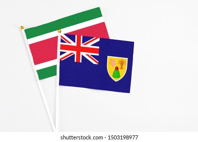 Turks And Caicos Islands and Suriname stick flags on white background. High quality fabric, miniature national flag. Peaceful global concept.White floor for copy space.