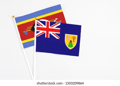 Turks And Caicos Islands and Swaziland stick flags on white background. High quality fabric, miniature national flag. Peaceful global concept.White floor for copy space.