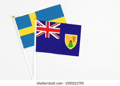 Turks And Caicos Islands and Sweden stick flags on white background. High quality fabric, miniature national flag. Peaceful global concept.White floor for copy space.