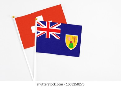 Turks And Caicos Islands and Switzerland stick flags on white background. High quality fabric, miniature national flag. Peaceful global concept.White floor for copy space.