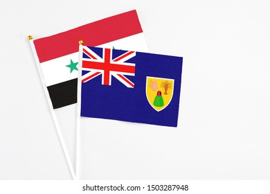 Turks And Caicos Islands and Syria stick flags on white background. High quality fabric, miniature national flag. Peaceful global concept.White floor for copy space.