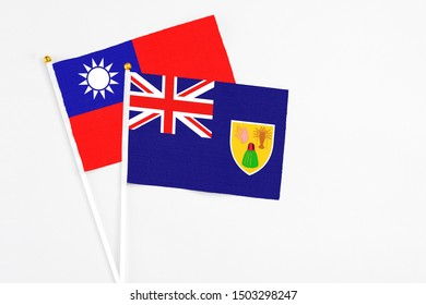 Turks And Caicos Islands and Taiwan stick flags on white background. High quality fabric, miniature national flag. Peaceful global concept.White floor for copy space.
