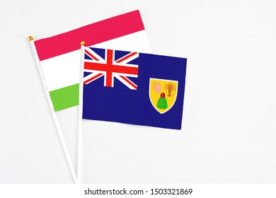 Turks And Caicos Islands and Tajikistan stick flags on white background. High quality fabric, miniature national flag. Peaceful global concept.White floor for copy space.