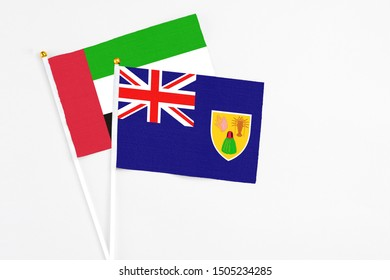 Turks And Caicos Islands and United Arab Emirates stick flags on white background. High quality fabric, miniature national flag. Peaceful global concept.White floor for copy space.