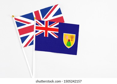 Turks And Caicos Islands and United Kingdom stick flags on white background. High quality fabric, miniature national flag. Peaceful global concept.White floor for copy space.