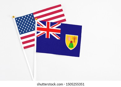 Turks And Caicos Islands and United States stick flags on white background. High quality fabric, miniature national flag. Peaceful global concept.White floor for copy space.