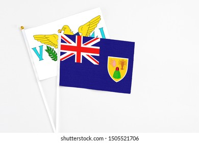 Turks And Caicos Islands and United States Virgin Islands stick flags on white background. High quality fabric, miniature national flag. Peaceful global concept.White floor for copy space.