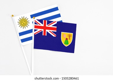Turks And Caicos Islands and Uruguay stick flags on white background. High quality fabric, miniature national flag. Peaceful global concept.White floor for copy space.