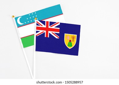 Turks And Caicos Islands and Uzbekistan stick flags on white background. High quality fabric, miniature national flag. Peaceful global concept.White floor for copy space.