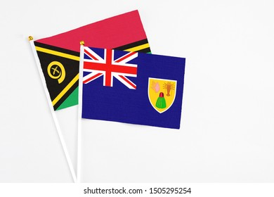 Turks And Caicos Islands and Vanuatu stick flags on white background. High quality fabric, miniature national flag. Peaceful global concept.White floor for copy space.