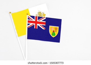 Turks And Caicos Islands and Vatican City stick flags on white background. High quality fabric, miniature national flag. Peaceful global concept.White floor for copy space.