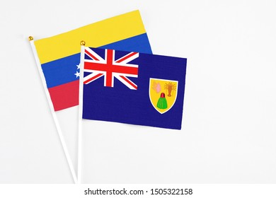 Turks And Caicos Islands and Venezuela stick flags on white background. High quality fabric, miniature national flag. Peaceful global concept.White floor for copy space.