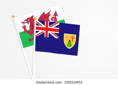 Turks And Caicos Islands and Wales stick flags on white background. High quality fabric, miniature national flag. Peaceful global concept.White floor for copy space.