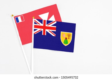 Turks And Caicos Islands and Wallis And Futuna stick flags on white background. High quality fabric, miniature national flag. Peaceful global concept.White floor for copy space.