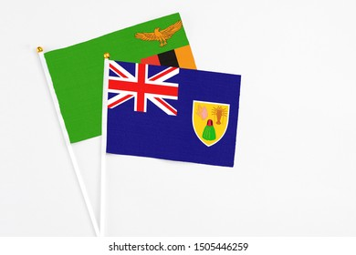 Turks And Caicos Islands and Zambia stick flags on white background. High quality fabric, miniature national flag. Peaceful global concept.White floor for copy space.