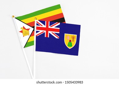 Turks And Caicos Islands and Zimbabwe stick flags on white background. High quality fabric, miniature national flag. Peaceful global concept.White floor for copy space.