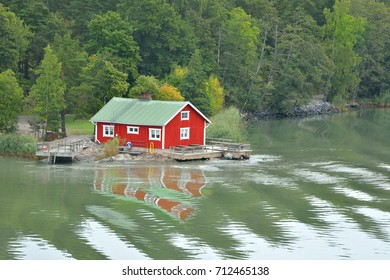 TURKU, ARCHIPELAGO, FINLAND - SEPTEMBER 2, 2017: Red wooden traditional Finnish house and pier on bank of island