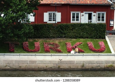TURKU, FINLAND - AUGUST 1, 2017: the name of the Turku City made of flowers on riverbank of Aura river with girl sitting on green grass