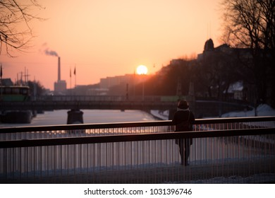 TURKU, FINLAND - FEBRUARY 18th, 2018 - A woman standing on Kirjastosilta Bridge and looking at golden sunset over Aura River