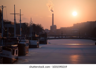 TURKU, FINLAND - FEBRUARY 18th, 2018: Golden sunset at winter  over Aura river with the popular river boat restaurants on the frozen river and Turku Energia chimney in the background.