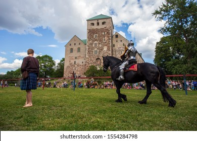 Turku / Finland - July 9, 2018: Knights in armor compete in a jousting tournament in front of Turku Castle.