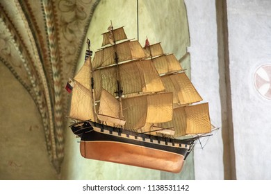 Turku / Finland - June 24 2018:  Traditional sail boat suspended from arched ceiling, in Turku Cathedral, in Turku, Finland, during midsummer.