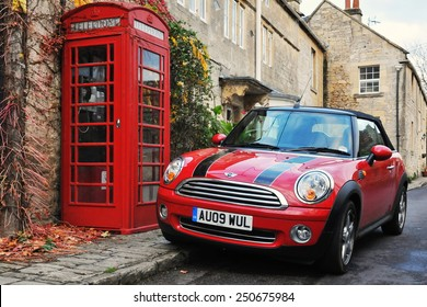 TURLEIGH - NOV 6: View of a Mini Cooper car and traditional red phone box on a village street on Nov6, 2010 in Turleigh, UK. The mini and red phone boxes are uniquely British design icons.