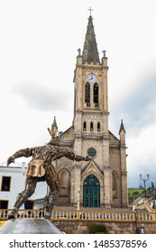 TURMEQUE, COLOMBIA – AUGUST, 2019: Our Lady of Chiquinquira church and the Monument to Chaquen the god of sports and fertility in the religion of the Muisca playing Colombian game called tejo