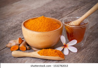 Turmeric ( curcumin, Curcuma longa Linn) powder in wooden bowl and scoop with rhizome and glass of honey isolated on old wood table background. Beauty and spa concept.