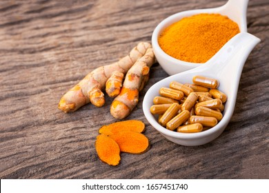 Turmeric ( curcumin, Curcuma longa Linn) powder in white cera bowl and tumeric capsule with root and slice isolated on wood background. Supplement concept. Top view.