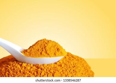 turmeric or curcumin longa root powder in spoon  in yellow background