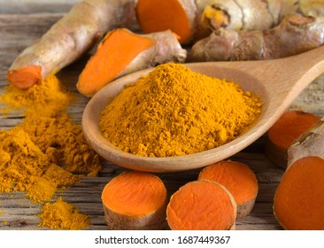 Turmeric (curcumin) powder and roots on a wooden background,Used for cooking and as herbal medicine.